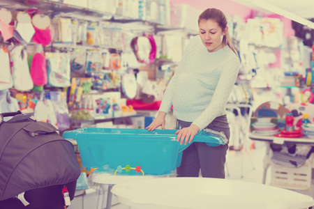 concentrated pregnant female is buying bath for baby in the children's goods store Standard-Bild