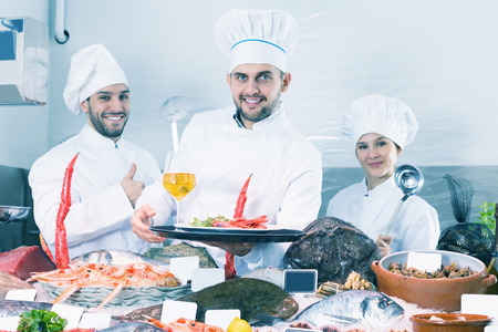 Smiling group of professional cooks of fish restaurant inviting to degustation of dishes of seafood