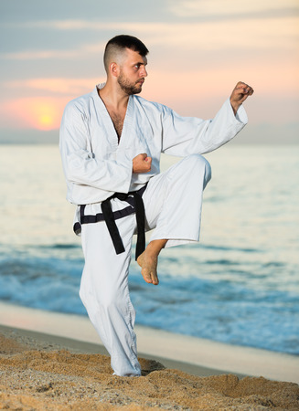 Young male doing karate at ocean quay outdoor