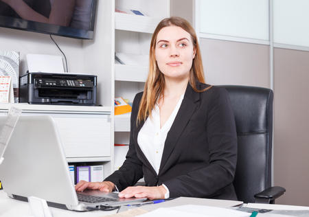 Young smiling saleswoman working on laptop in furniture salon