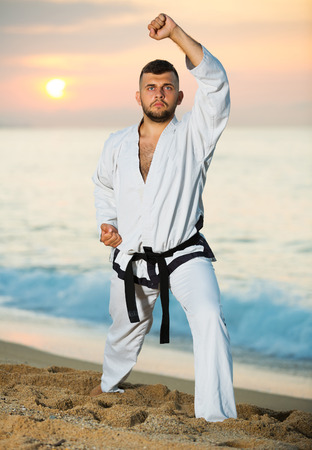Active adult man doing karate poses at  sunset sea shore
