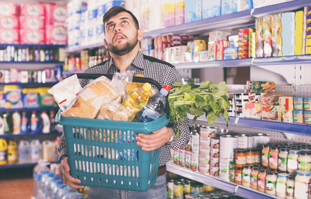 Tired young man with heavy shopping basket filled food products in supermarket Banco de Imagens