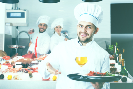Portrait of confident smiling chef in uniform standing with serving tray in fish restaurant