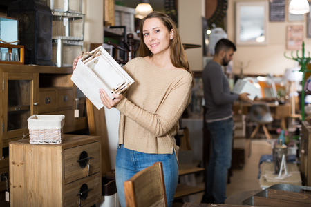 Smiling girl with friend visiting furniture shop in search of interest things for home interior