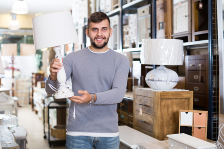 Young man satisfied with purchase of stylish table lamp in furniture store Stockfoto