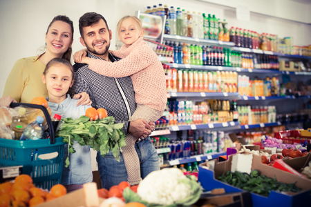 Two positive little sisters during family shopping in greengrocery department of supermarket Stock Photo