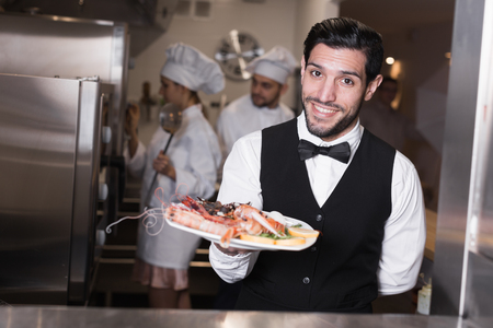 Cheerful waiter with plate of delicious seafood dishes in kitchen of fish restaurant