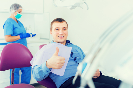 portrait of male visitor sitting and smiling in dentists office
