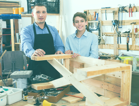 Smiling adult woodworker and pupil making furniture in workshop Stock Photo