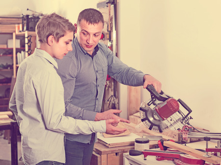 happy french father and son with  fret saw cutting wood plank in  garage