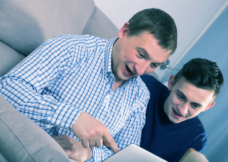 Man with his adult son are playing on laptop together at the home.