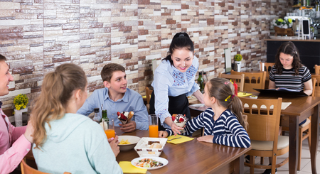 Polite attractive waitress serving dishes to family in cafe Фото со стока
