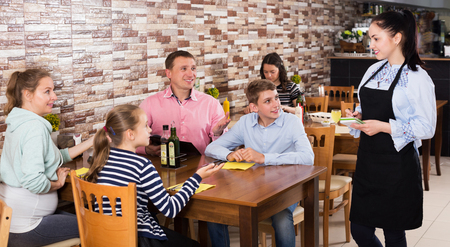 Happy adult waitress taking order from guests and writing into note