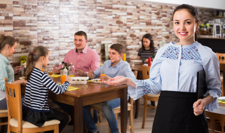 joyous young waitress warmly welcoming guests to comfortable family cafe