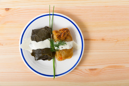 Top view of delicious dolma and stuffed cabbage served with sour cream and fresh greens on wooden background Banque d'images