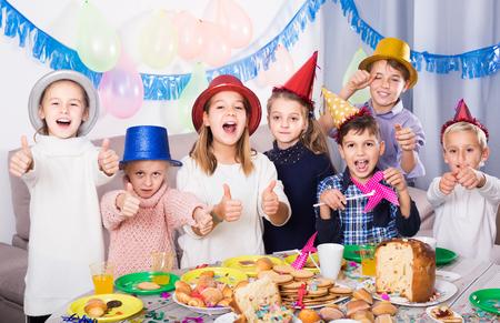 Smiling russian children having celebration of friend's birthday during dinner