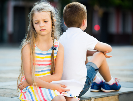 upset girl in preschool age having problem with friend outdoors in park