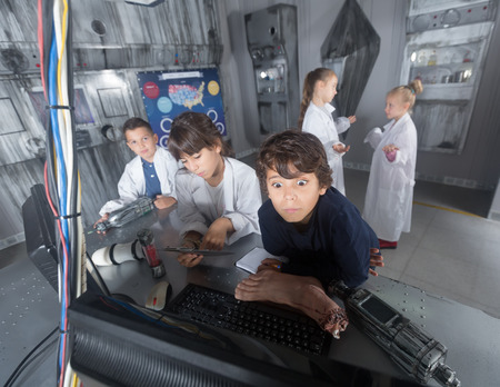 concentrated schoolkids solve task in the bunker quest room
