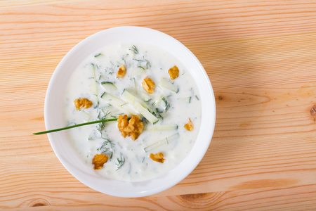 Top view of traditional Bulgarian cold vegetable soup Tarator served in white bowl on wooden background 版權商用圖片