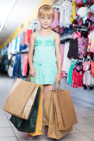 little blonde girl holding packages with wear for children in the shop Stock Photo