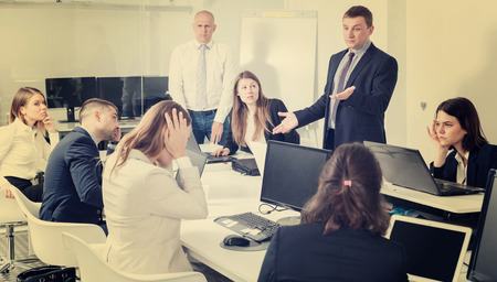Serious manager expressing dissatisfaction with teamwork of colleagues at meeting
