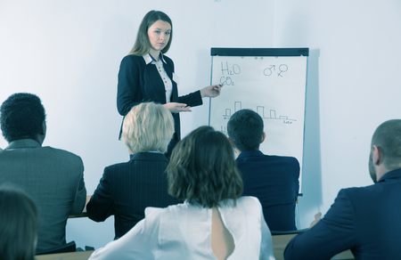 Confident young woman speaking on corporate business meeting in boardroom