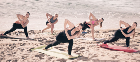 Group of women exercising yoga on sea beach on sunny day 写真素材