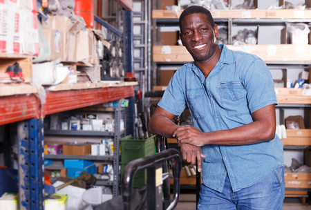 Portrait of satisfied African American purchaser standing among shelves in building materials store