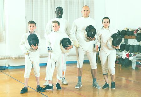 Portrait of happy mixed age group of athletes with foils at fencing workout Stock Photo