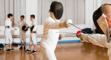 Closeup portrait of young fencer in mask practicing lunge with foil during fencing workout in gym Stock Photo