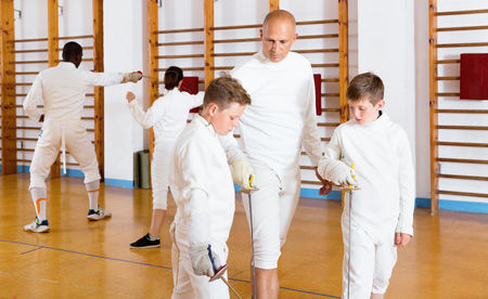Focused diligent serious boys fencers attentively listening to professional  friendly fencing coach in gym