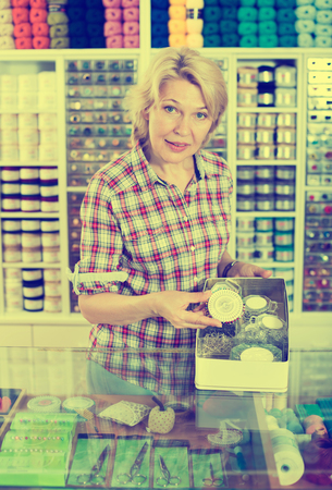 Mature smiling woman seller standing at counter with small pins in sewing store