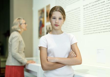 Attentive teenage girl exploring artworks in modern museum
