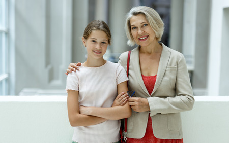 Attentive tween girl with senior woman looking with interest at gallery exposition Stock Photo