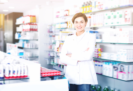 Female pharmacist displaying assortment of products in pharmacy