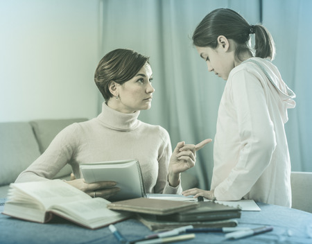 Mother does remarks daughter for incorrectly solved school homeworks Stock Photo