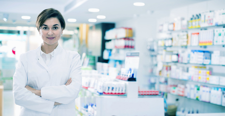 Young diligent friendly female pharmacist arranging displayed assortment in pharmacy Standard-Bild