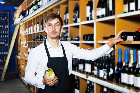 Happy young man seller wearing uniform having bottle of wine in wine house
