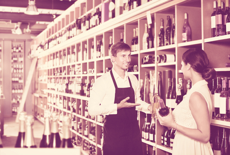 Young man seller wearing uniform helping woman customer with bottle of wine at the wine house