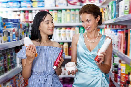 Jolly woman and girl looking different haircare products at cosmetics shop