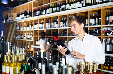 portrait of young american glad male customer taking bottle of wine in store