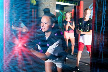 Portrait of teenager girl with laser gun having fun on dark lasertag arena