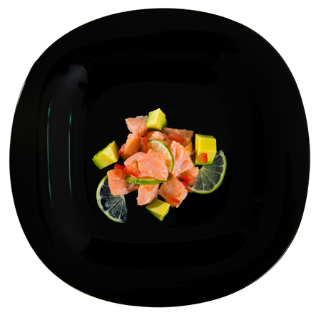 Black plate with delicious salmon ceviche with avocado and lime. Isolated over white background Stock Photo
