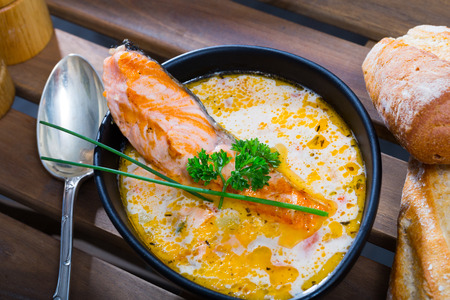 Picture of  delicious cream-soup with salmon and greens, served  in bowl with bread at table
