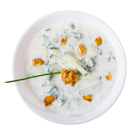 Top view of traditional Bulgarian cold vegetable soup Tarator served in white bowl . Isolated over white background