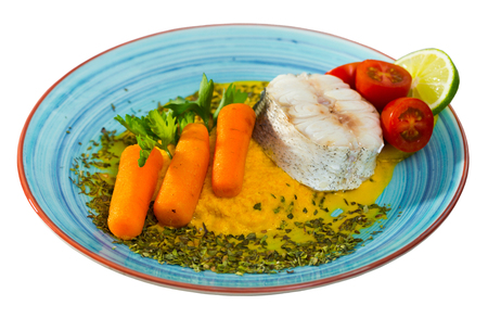 Steamed merluccius served with vegetable pate. Recipe: carrots, onion and garlic bake and beat in blender, add olive oil and salt. Fish steak 250g steam for 15 minutes. Serve with pate, greens, lemon. Isolated over white background
