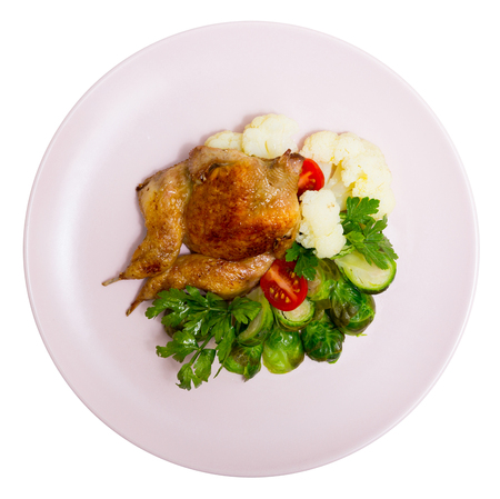 Top view of tobacco quail on cushion of steamed cauliflower and Brussels sprout, fresh tomatoes and aromatic greens. Isolated over white background Stock Photo