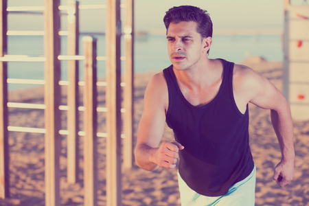 Concentrated athletic man running on seashore in daytime