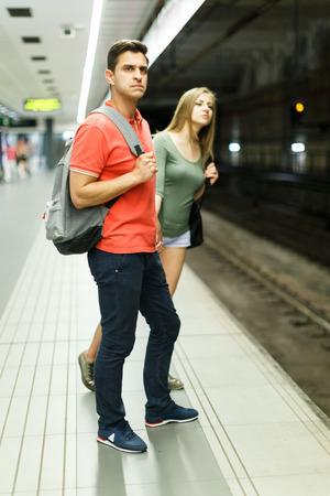 Couple is standing on platform and waiting train in the underground.