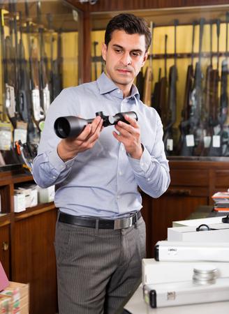 hombre confiado que mira a los botones ópticos para la caza en la tienda